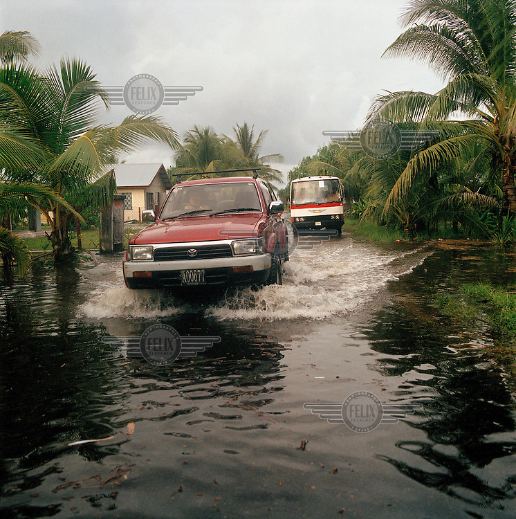 A car and a bus maake their way through the high floodwaters which have inundated the low-lying atoll during a high spring tide.