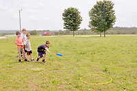 RACHEL DICKERSON/MCDONALD COUNTY PRESS Students in Beverly Jackson's class at White Rock School take turns trying to toss a flying disc into a ring. Summer school allows kids to be active.