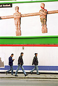 Three men walk past an advertising hoarding in Praed Street, Paddington, London.