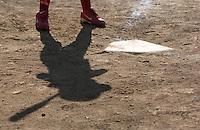 A girls softball league batter's shadow is cast across home plate.