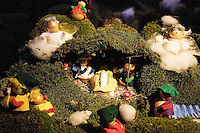 "Switzerland. Canton Tessin. Vira Gambarogno. The old town shows an exhibit of various Nativity scenes, illuminated at night for the Christmas holiday season. A Nativity Scene, may be used to describe any depiction of the Nativity of Jesus in art, but in the sense covered here, also called a crib or in North America and France a crèche (meaning ""crib"" or ""manger"" in French). It means a three-dimensional folk art depiction of the birth or birthplace of Jesus, either sculpted or using two-dimensional (cut-out) figures arranged in a three-dimensional setting. Christian nativity scenes, in two dimensions (drawings, paintings, icons, etc.) or three (sculpture or other three-dimensional crafts), usually show Jesus in a manger, Joseph and Mary in a barn (or cave.  © 2007 Didier Ruef"
