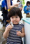 Ai Nakahodo, 3, a volunteer participating in the Team Tyura Sango coral reef restoration project, shows off her piece of coral attached to a ceramic name tag that will be placed into coral nurturing tanks before being bolted to the sea bed in the nearby bay in Onna Village, Okinawa Prefecture, Japan, on Saturday, June 23, 2012.   Coral seedlings are put on small plates made of coral-like components, then fixed in place by wire and given a registration  number. They are raised at an aquafarm for several months before being bolted to the sea floor. Photographer: Robert Gilhooly