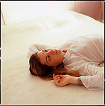 Girl, laying on top of bed facing up