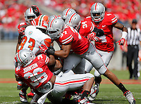 A slew of Buckeye defenders including linebacker Trey Johnson (36) and linebacker Joshua Perry (37) tackle Florida A&M Rattlers wide receiver Admasen Felix (83) during the second quarter of the NCAA football game at Ohio Stadium in Columbus on Sept. 21, 2013. (Adam Cairns / The Columbus Dispatch)