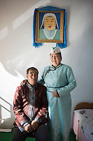 Mongolian herder Renqima and husband Tegan Bayar wear national costume and pose underneath a portrait of Genghis Khan before they headed for the traditional festival of Naadam in Damao Banner, Inner Mongolia, China, October 2014.