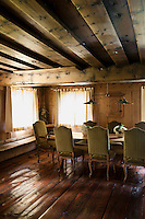 The dining room has a low beamed ceiling, wood panelling and weathered wooden floorboards