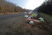 A roadside memorial of a cross, markers and arrangements of plastic flowers marks the site of a fatal vehicle accident along a divided highway in rural West Virginia.<br />
