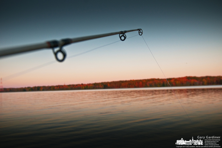 A fisherman's reel is framed against the dark sky as the sun sets over a lake on a fall day.