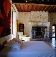 A large red and orange tapestry woven by Pierre Clerk hangs above the bed in the master bedroom which has a large open fireplace