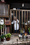 Tokyo, June 25 2013 -  Old lady going out of her house in the Nezu area.