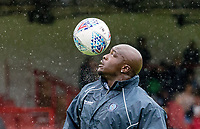 Adebayo Akinfenwa of Wycombe Wanderers warms up in the rain ahead of the pre season friendly match between Aldershot Town and Wycombe Wanderers at the EBB Stadium, Aldershot, England on 22 July 2017. Photo by Andy Rowland.