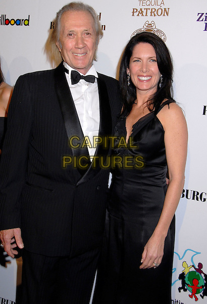 DAVID CARRADINE & ANNIE BIERMAN .June 4th 2009: David Carradine, 72, was found dead in his Bangkok, Thailand hotel room..File Photo:  Billboard and Children Uniting Nations 9th Annual Awards Celebration Viewing Dinner and Oscar After Party held at the Beverly Hilton Hotel, Beverly Hills, California, USA, 24th February 2008..Half length black dress tuxedo tux bow tie husband wife dead died couple .CAP/ADM/GB.©Gary Boas/Admedia/Capital Pictures