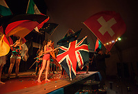 Switzerland. Canton Ticino. Tenero. Camping Campofelice. Every Friday night in the Pavillon takes place a performance show by the children who attended the Circus school during their one week stay in the campsite. The circus has been ran for the last twenty years by the french artist, Bruno Prin (R), who hold in his hands a Swiss flag.  The flag of Switzerland consists of a red flag with a white cross (a bold, equilateral cross) in the centre. It is one of only two square sovereign-state flags. A young girl holds on stage the Union Jack, also known as the Union Flag, which is the national flag of the United Kingdom. The Union Jack consists of the red cross of Saint George (patron saint of England), edged in white, superimposed on the Cross of St Patrick (patron saint of Ireland), which are superimposed on the Saltire of Saint Andrew (patron saint of Scotland). A girl holds the German Flag. The flag of Germany is a tricolour consisting of three equal horizontal bands displaying the national colours of Germany: black, red, and gold. A girl holds the  European Flag which is an official symbol of two separate organisations— the Council of Europe (CoE) and the European Union (EU). It consists of a circle of twelve five-pointed yellow (or) stars on a blue (azure) field. 20.07.2018 © 2018 Didier Ruef