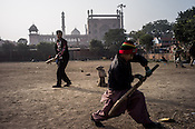 Young boys cricket in a small dusty ground outside the Jama Masjid mosque in Meena Bazaar in Old Delhi, India.