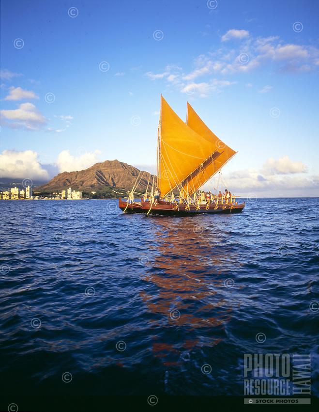 Traditional Hawaiian sailing canoe, the Hawaii loa off the gold coast of Oahu with Diamond head in rear