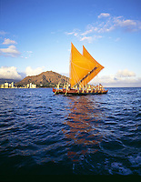 Traditional Hawaiian sailing canoe, the Hawaii loa off the gold coast of Oahu with Diamond head in rear