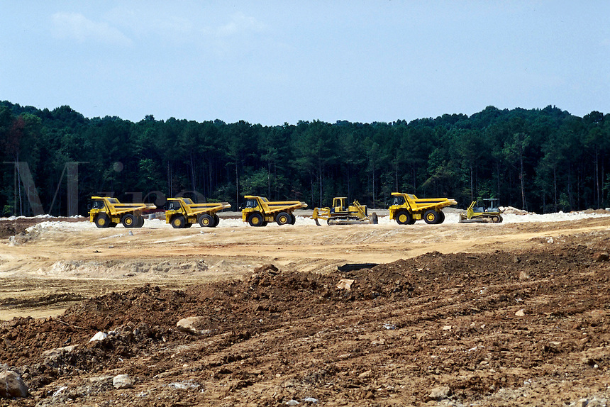Dump trucks and bulldozers are lined up ready to build at a vast construction project. Urban transformation.