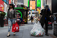 NEW YORK, NY - APRIL 2: A woman carries her shopping  plastic bag as she walks along Times Square as a homeless uses a plastic bag to recycle on April 2, 2019 in New York. New York will become the second state in U.S. to ban shops from providing single-use plastic bags for most purchases.   (Photo by Eduardo MunozAlvarez/VIEWpress)