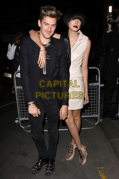 HENRY HOLLAND & AGYNESS DEYN.The Vogue Dinner Party at La Caprice Restaurant, London, England..September 21st, 2009.full length black white leather dress dark dyed hair red lipstick shoes strappy sandals jacket jeans denim arm over shoulder  .CAP/AH.©Adam Houghton/Capital Pictures.