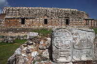 "The Codz Poop?s Altar of the Glyphs, square layout of 21 feet on each side, four faces with carved, bas-relief glyphs, western façade of the Codz Poop (""Rolled-up matting"" in Maya) in the background, Puuc Architecture, 700 ? 900 AD, Kabah, Yucatan, Mexico. Picture by Manuel Cohen"