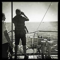 Sea Watch-2.<br /> Die Sea Watch-2 bei ihrer 13. SAR-Mission vor der libyschen Kueste.<br /> Im Bild: Ein Mitglied der Crew beobachtet mit dem Fernglass  ein Schlauchboot mit ca. 160 Menschen.<br /> 20.10.2016, Mediterranean Sea<br /> Copyright: Christian-Ditsch.de<br /> [Inhaltsveraendernde Manipulation des Fotos nur nach ausdruecklicher Genehmigung des Fotografen. Vereinbarungen ueber Abtretung von Persoenlichkeitsrechten/Model Release der abgebildeten Person/Personen liegen nicht vor. NO MODEL RELEASE! Nur fuer Redaktionelle Zwecke. Don't publish without copyright Christian-Ditsch.de, Veroeffentlichung nur mit Fotografennennung, sowie gegen Honorar, MwSt. und Beleg. Konto: I N G - D i B a, IBAN DE58500105175400192269, BIC INGDDEFFXXX, Kontakt: post@christian-ditsch.de<br /> Bei der Bearbeitung der Dateiinformationen darf die Urheberkennzeichnung in den EXIF- und  IPTC-Daten nicht entfernt werden, diese sind in digitalen Medien nach &sect;95c UrhG rechtlich geschuetzt. Der Urhebervermerk wird gemaess &sect;13 UrhG verlangt.]