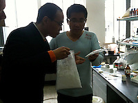 Eric Chang (L), 35, owner of CEC Limited, a company which exports MDPV, a legal high, to Great Britain, is seen checking bags of an unidentified 'new product' with a member of his staff, (R), in his laboratory in Pudong, Shanghai, China, 08 April 2010.