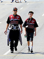 Jul. 20, 2014; Morrison, CO, USA; NHRA top fuel driver Larry Dixon (left) walking with his son Donovan Dixon during the Mile High Nationals at Bandimere Speedway. Mandatory Credit: Mark J. Rebilas-