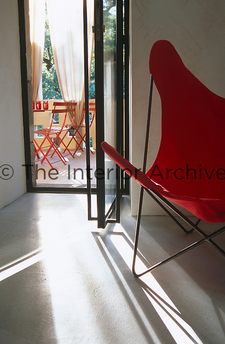 A red Butterfly chair stands by an open glass door