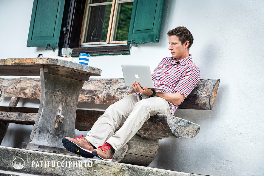 David Göttler using a laptop computer and relaxing outside with a cup of coffe while traveling.
