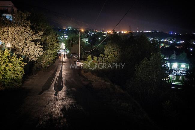 28/06/14. Shaqlawa, Iraq. -- A view of Shaqlawa at night with two Internally displaced people walking up the hill.