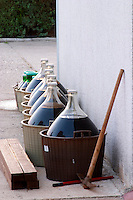 Line of demijohns with wine standing outside the winery exposed to the sun. Hercegovina Produkt winery, Citluk, near Mostar. Federation Bosne i Hercegovine. Bosnia Herzegovina, Europe.
