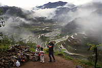 An Ifugao family with the Banaue Rice Terraces in the background. Ifugaos are one of the ethno-linguistic groups residing in the Philippine Cordillera at the northeastern part of main island of Luzon, Philippines. The Banaue Rice Terraces, declared a World Heritage Site, is one of the tourist attractions in the Philippines. Banaue, Ifugao. 22 February 2001
