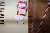 "Signs near the door separating the ""green zone"" from the ""red zone"" read, ""High risk zone, full PPE required"" and ""Suspect patient's ward."" Occidental College professor Mary Beth Heffernan works on her PPE Portrait Project with health care workers at the ELWA II ETU (Ebola treatment unit) in Monrovia, Liberia on Saturday, March 8, 2015.<br /> (Photo by Marc Campos, Occidental College Photographer) Mary Beth Heffernan, professor of art and art history at Occidental College, works in Monrovia the capital of Liberia, Africa in 2015. Professor Heffernan was there to work on her PPE (personal protective equipment) Portrait Project, which helps health care workers and patients fighting the Ebola virus disease in West Africa.<br />