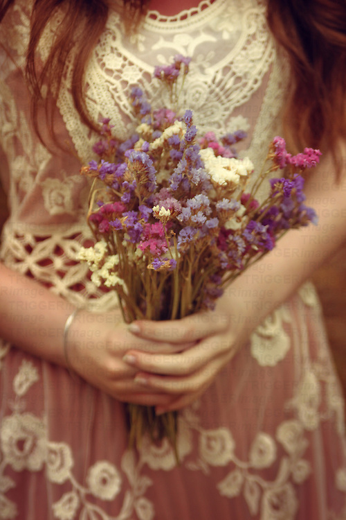 Close-up of a young girl's hands holding a bouqet of wild spring flowers