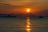 A fishing boat and the Oropos to Eretria ferry boat sail as the sun sets -marking the longest day of the year during the summer solstice- over the seaside port town of Oropos, 30 miles (50 km) north of Athens, Greece. Friday 21 June 2019