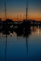 Sail boats and their reflections at sunset, moored at San Leandro Marina on San Francisco Bay.