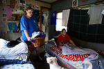 Wendy Haddix carries laundry in her home in Breathitt County, Ky., on Friday, Oct. 14, 2011. Haddix sleeps on the couch while her daughter, Nicole Hensley, sleeps on a bed in the same room. Photo by Latara Appleby