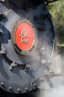 Fine art detail of grey 1924 steam locomotive engine, Quincey No. 2 of the American Locomotive Company, with red center and name plate, with steam surrounding the front of engine,  returned to service for first time since 1950, on Niles Canyon Railway in northern California.