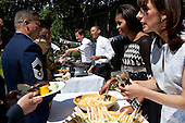 President Barack Obama, British Prime Minister David Cameron, First Lady Michelle Obama, and Samantha Cameron serve military families during a barbecue in the garden at 10 Downing Street in London, England, May 25, 2011. .Mandatory Credit: Pete Souza - White House via CNP