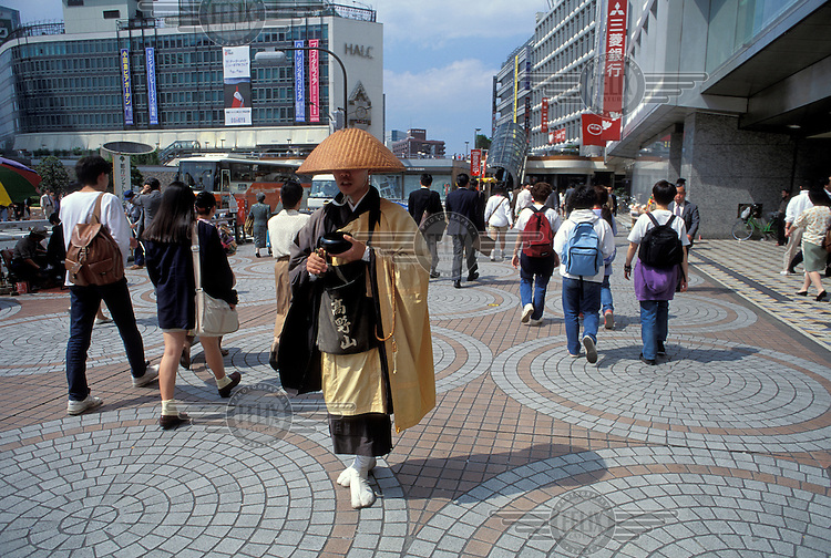 Zen Buddhist monk asking for alms from passers-by in the busy Shinjuku district.