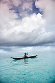 INDONESIA, Mentawai Islands, Kandui Resort, fisherman Gesayas Ges paddling his dugout canoe against a cloudy sky