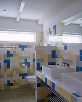 A selection of coloured tiles laid in a random pattern gives a great sense of disorder to this well-planned bathroom