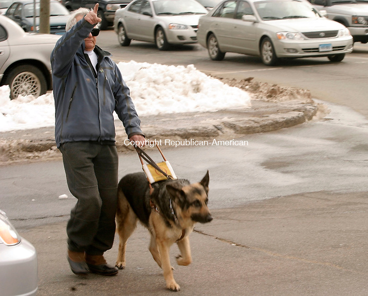 WATERBURY, CT- 25 MARCH 2005-032505J04--Waterbury resident John Casolo and his guide dog Gregger, cross the street at the corner of Meriden and Frost Road in Waterbury. Casolo, 72, is blind and has trouble crossing at the intersection and is asking of audible traffic signals at major intersections.--- Jim Shannon Photo-- John Casolo; Waterbury; Gregger, Meriden,  Frost Road are CQ