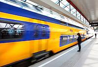 Trein stopt  bij het perron van  een station