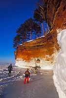 A family explores the ice-covered sea caves of Lake Superior at Squaw Point in Apostle Islands National Lakeshore near Bayfield, Wis.