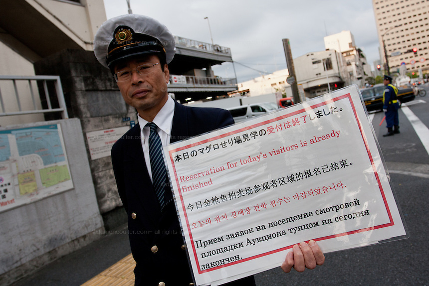 A security guard holds a sign saying that reservations for the tuna auctions has already finished as tourists flock to the tuna auctions in Tsukiji whiolesale fish market as it reopens to tourists after being closed for one month. Tsukiji is the largest wholesale fish market in the world and a major tourist attraction in Tokyo. But visitor numbers have increased to a level now that is affacting the day to day running of the market and severe restrictions have been placed on the movement of tourists at its busiest time. Tsukiji, Tokyo, Japan. May 10th 2010