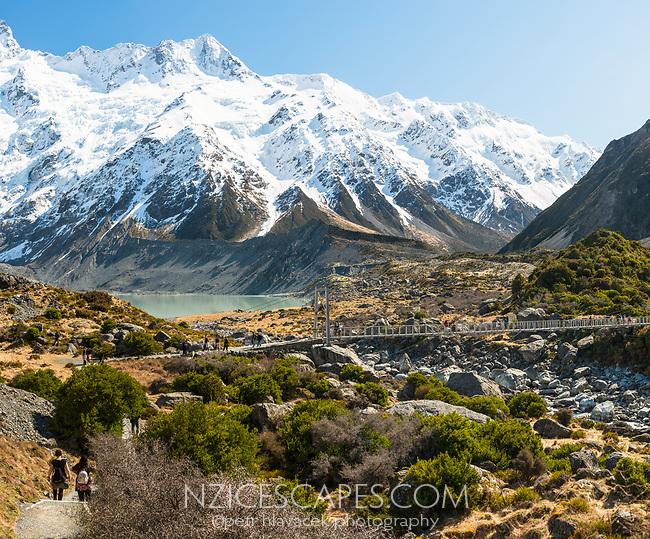 Hikers hiking on track near Mueller Lake and swingbridge, Aoraki, Mount Cook National Park, UNESCO World Heritage Area, Mackenzie Country, South Island, New Zealand, NZ