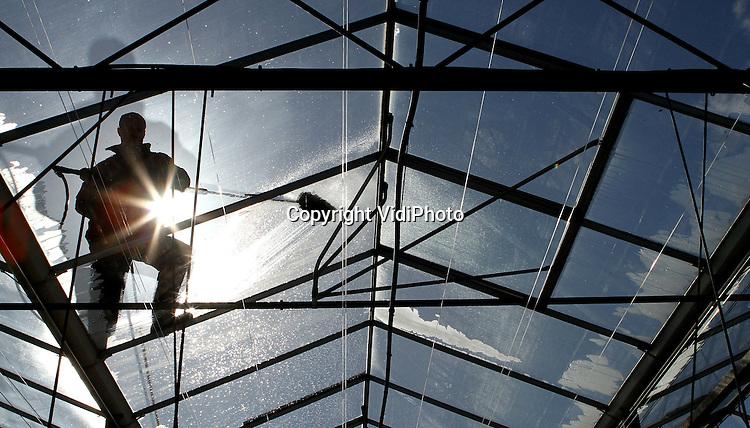 Foto: VidiPhoto..DOORNENBURG - Personeel van aarbeienteler Arno de Beijer uit Doornenburg verwijdert donderdag algen- en roetaanslag op het dak van de aardbeienkassen nog op de ouderwetse wijze: met de hand. Iedere procent meer licht is ook een procent meer opbrengt, berekent hij. Licht is winst, vooral omdat de zon zich nog nauwelijks heeft laten zien de eerste twee maanden van het jaar. De aardbeienoogst begin daarom ook later dan gebruikelijk.