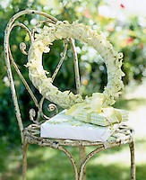 Detail of a wrought-iron chair in the garden with a spring wreath decorated with green and white gingham ribbons and presents