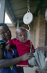 A mother put her baby on the weight scale. The nurse will then orient the mother and her child to the right child health service at the Butera health centre, district of Burera, Rwanda